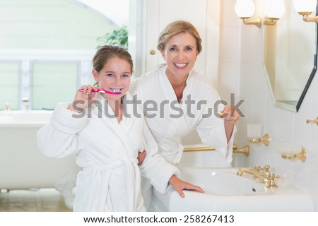 Happy mother and daughter brushing teeth together in the bathroom - stock photo