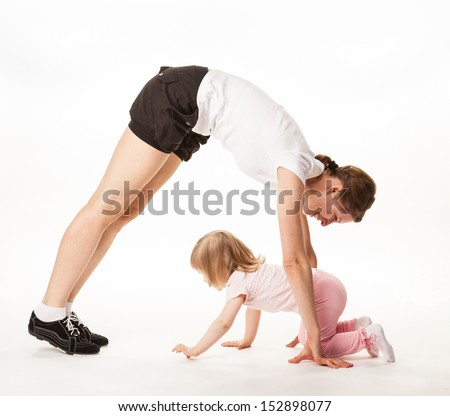 Happy mother and daughter doing sport exercises together on white background - stock photo