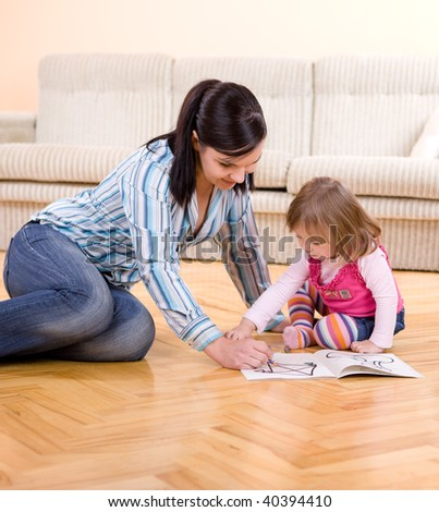happy mother and daughter drawing at home - stock photo