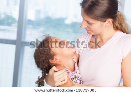 Happy mother and daughter embracing each other indoor - stock photo