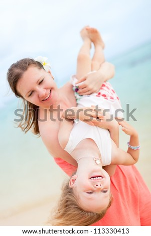 Happy mother and daughter having fun outdoors - stock photo
