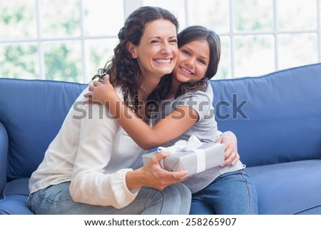 Happy mother and daughter hugging and smiling at camera in the living room - stock photo