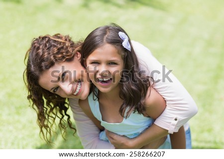 Happy mother and daughter hugging in the garden - stock photo