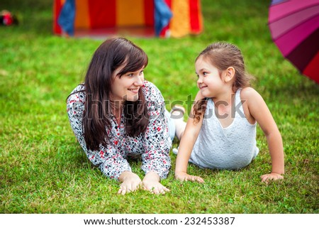 Happy mother and daughter in a park - stock photo
