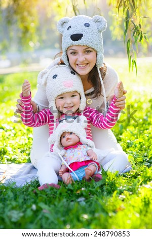 happy mother and daughter in a park wearing a knit hat. - stock photo