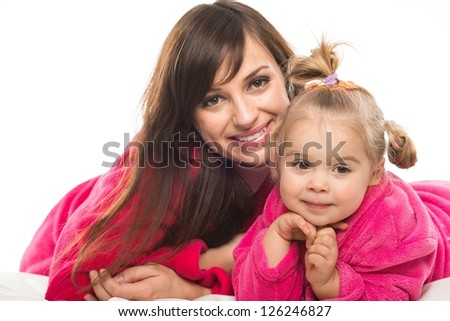 Happy mother and daughter in dressing gowns - stock photo