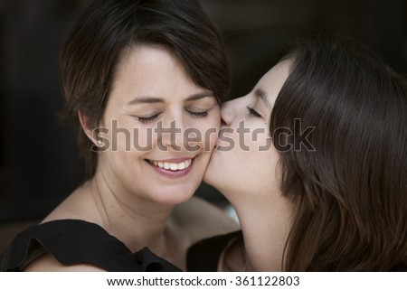 Happy mother and daughter kissing - stock photo