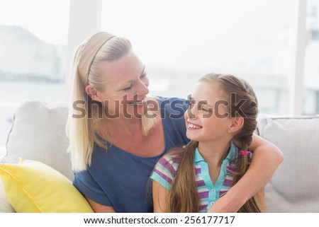 Happy mother and daughter looking at each other while sitting on sofa at home - stock photo