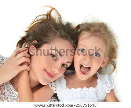 Happy mother and daughter lying on the floor laughing together hugging smiling isolated on a white background - stock photo