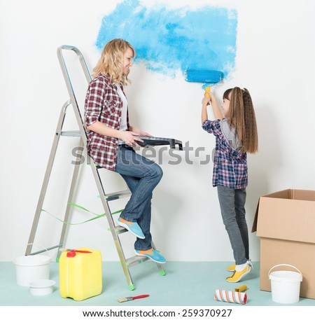 Happy mother and daughter makes repairs at home. Smiling girl painting wall at room. - stock photo