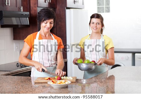 happy mother and daughter making fruit salad in kitchen - stock photo