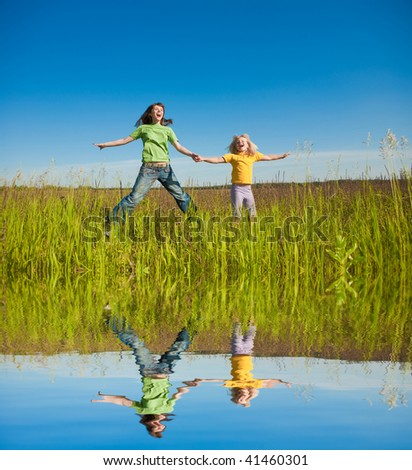 Happy mother and daughter on field - stock photo