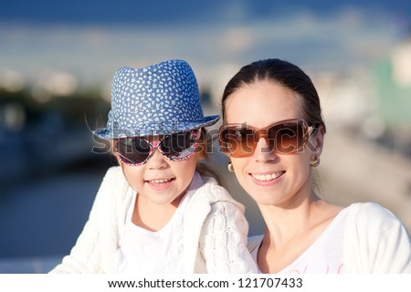 Happy mother and daughter outdoors in city on sunny summer day - stock photo