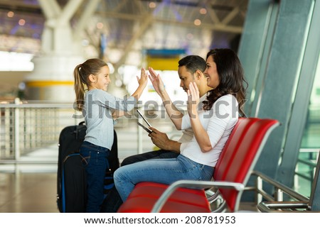 happy mother and daughter playing a game at airport before boarding - stock photo