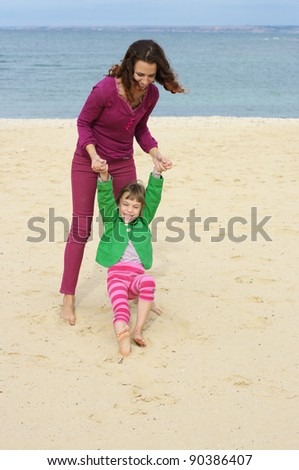 Happy mother and daughter playing at beach. - stock photo