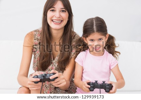 Happy mother and daughter playing video games on the couch - stock photo