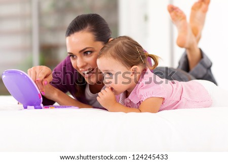 happy mother and daughter playing with toy laptop on bed - stock photo