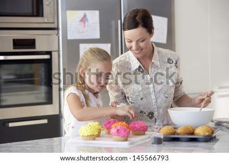 Happy mother and daughter preparing cupcakes in kitchen - stock photo