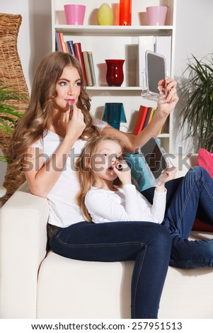 Happy mother and daughter putting makeup on together - stock photo