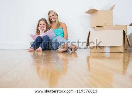 Happy mother and daughter reading a book together on the floor near moving boxes - stock photo