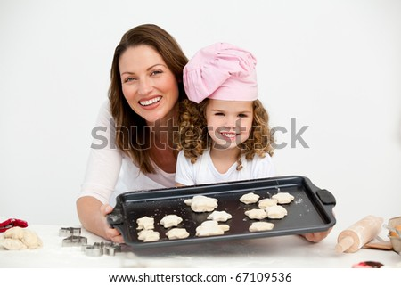Happy mother and daughter showing a plate with biscuits to the camera - stock photo