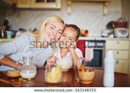 Happy mother and daughter sitting at table and looking at camera - stock photo