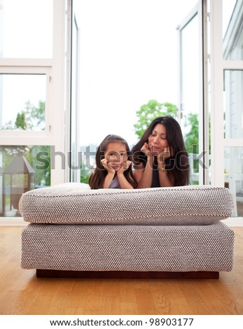 Happy mother and daughter sitting on a couch cushion with a smile, mother looking lovingly at daughter - stock photo