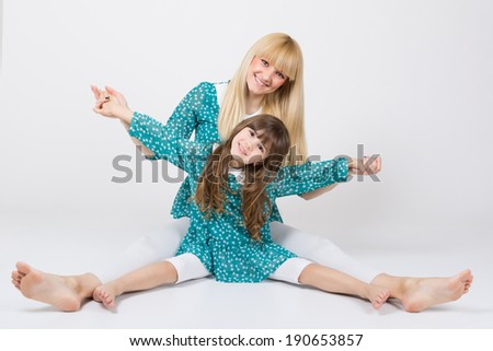 Happy mother and daughter sitting on the floor wearing matching outfit with bare feet having fun holding hands playing together. Family and Mother's day concept. - stock photo
