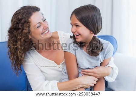 Happy mother and daughter smiling at each other in the living room - stock photo