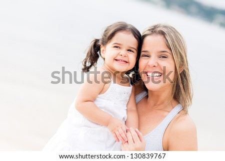Happy mother and daughter smiling at the beach - stock photo