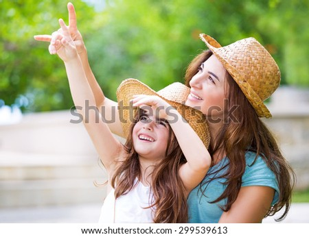 Happy mother and daughter spending time together outdoors, pointing fingers and enthusiastically looking up, with pleasure spending time in countryside - stock photo