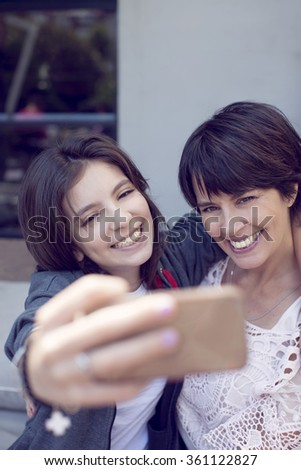 Happy mother and daughter taking a self portrait with mobile phone - stock photo