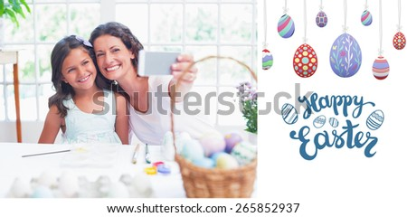 Happy mother and daughter taking selfie against happy easter graphic - stock photo