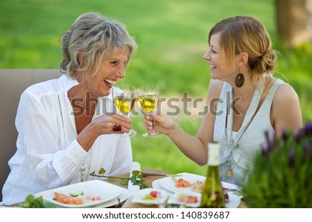 Happy mother and daughter toasting white wine at dining table in lawn - stock photo
