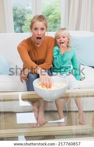 Happy mother and daughter watching tv at home in the living room - stock photo
