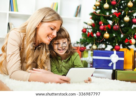 Happy mother and daughter with new year's tree and gift boxes, lying on floor and using tablet - stock photo