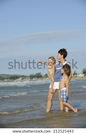 Happy mother and daughters having fun on the beach. - stock photo