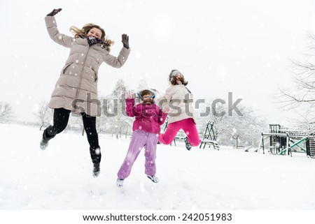Happy mother and daughters jumping in a wintry park - stock photo