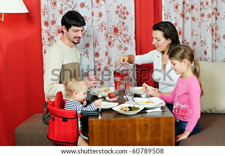 Happy mother and father and their two children eating at the dinner table - stock photo