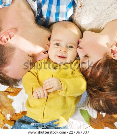 Happy mother and father kissing their daughter  - stock photo
