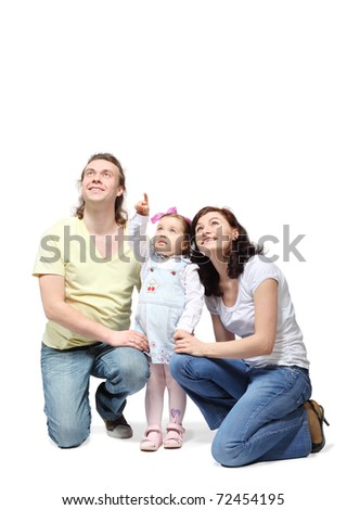Happy mother and father sit down and embrace little daughter which points fingers up - stock photo