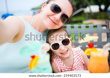 Happy mother and her adorable little daughter at outdoors cafe taking selfie while drinking tropical juice - stock photo