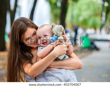 Happy mother and her baby-boy on hands play keeps teady bear toy outdoors in park. Happy young mother with her baby - stock photo