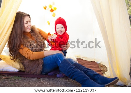 Happy mother and her baby posing sitting in tent outdoor. - stock photo
