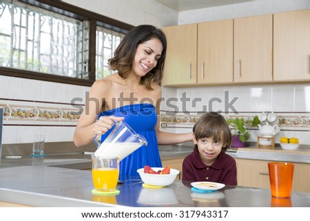 Happy Mother and her boy having breakfast in kitchen - stock photo