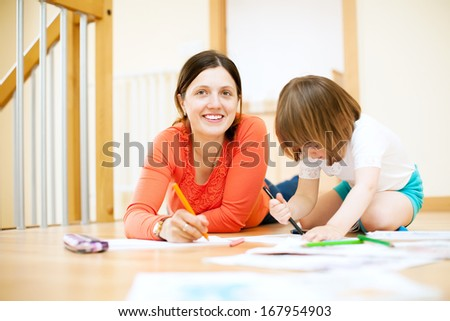 Happy mother and her child sketching on paper at parquet floor - stock photo