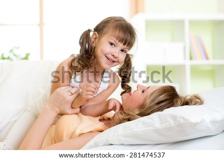 Happy mother and her child tickle, play and laugh in bed enjoying  sunny morning in bedroom - stock photo