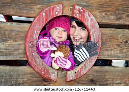 Happy mother and her daughter on winter playground - stock photo
