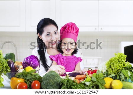 Happy mother and her daughter preparing a salad in their kitchen - stock photo