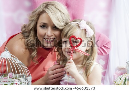 Happy mother and her little daughter looking through decorative heart toy - stock photo